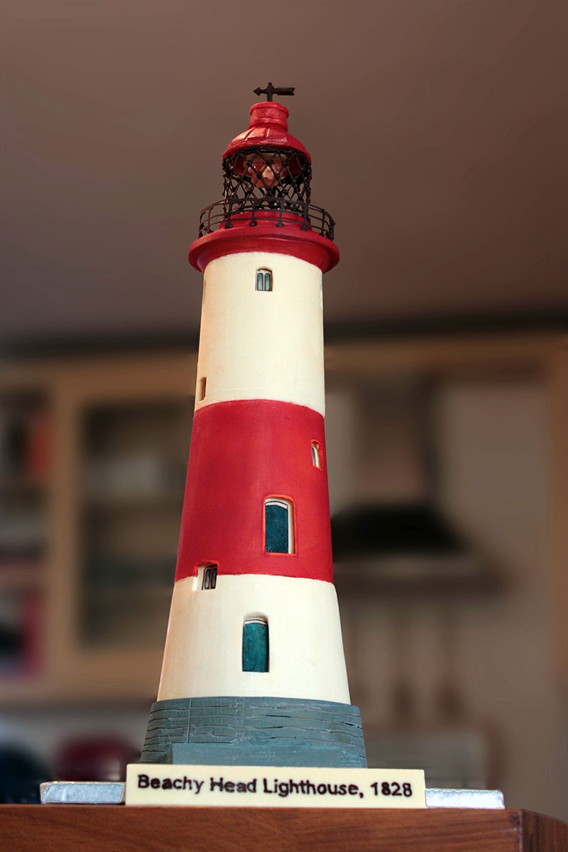 2 foot tall white chocolate Beachy Head light house coloured with alternating red and white stripes and the beacon light in the top with dark chocolate lattice work and a flashing led light