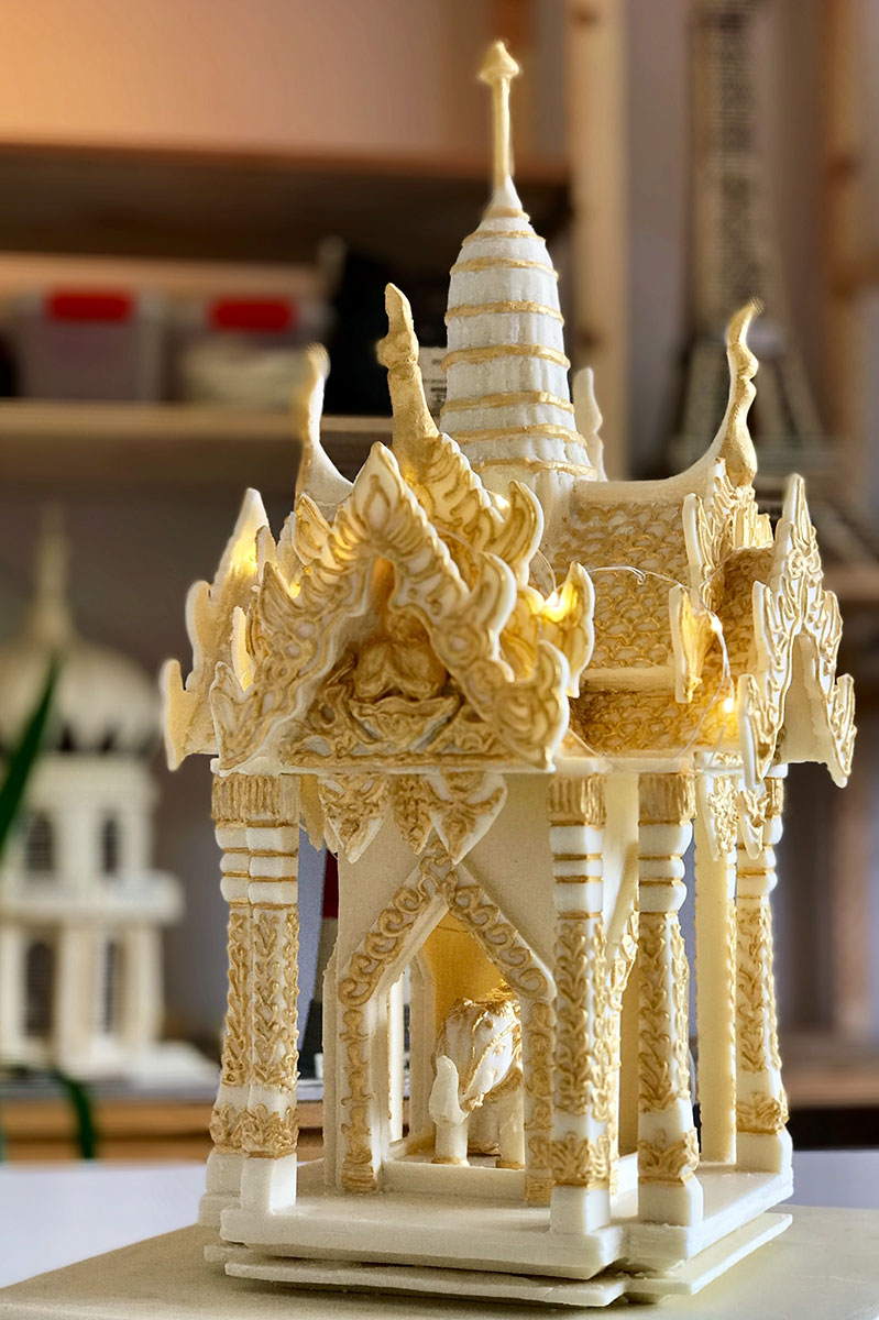 white chocolate and gold Thai shrine with lots of pillars, panels, details including and moulded elephant and four buddhas all decorated with edible gold dust