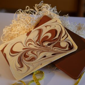The Big Swirly - two chunky chocolate tablets of 500g each - one is milk chocolate the other is a mix of white, dark and milk chocolate all swirled together creating a pretty pattern. tablets measures 254x152x10mm and are resting on a bed of straw with a yellow tape measure for size reference