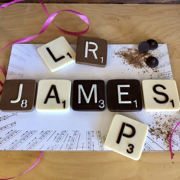 Chocolate Letter Tiles, milk, dark, white L R J A M E S P on a white placement with three dark chocolate buttons on the top right corner and pink raffia ribbon