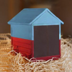 Brighton Beach Huts - Create Your Own - 250g at 7cm tall, 10cm deep of dark chocolate Brighton and Hove Beach Hut on a bed of straw. The roof and apexes have been painted with edible blue colour and the sides with red colour to look like the beach huts on Brighton sea front. You can choose the colours of the front doors or just keep them delicious dark chocolate