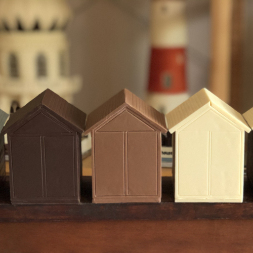 3 little brighton and hove beach huts in dark, milk and white chocolate with the brighton pavilion in the background