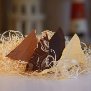 dark, milk , white, swirly mix options of Chocolate Shards around 8cm long, all four on a bed of straw