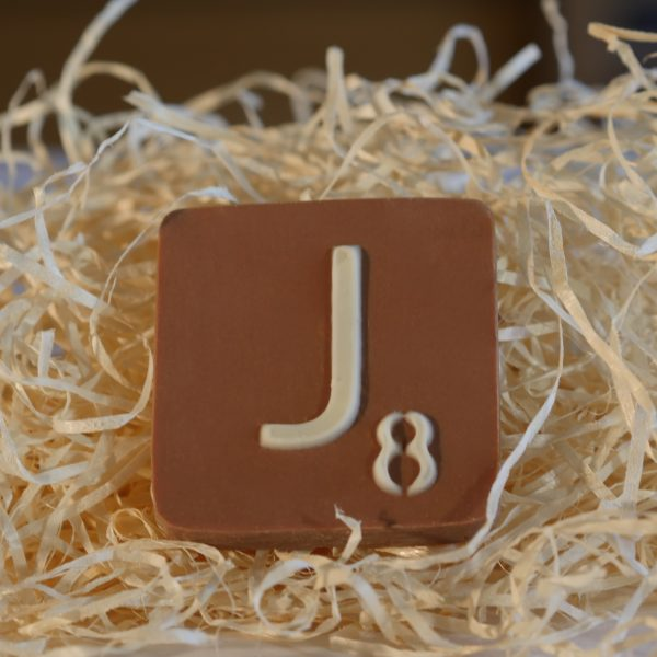 "40g milk chocolate letter ""J"" measures 6cm square by 1cm thick on a bed of biodegradable straw"