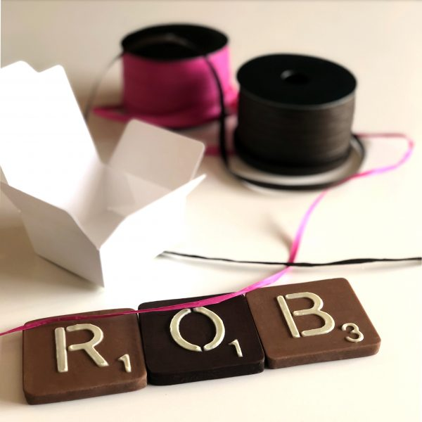 "40g milk and dark chocolate letters spelling ""ROB"" measuring 6cm square by 1cm thick with biodegradable small white chocolate box and pink and brown raffia ribbon spools"