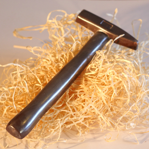 a realistic dark chocolate hammer tool dusted with edible silver shimmer