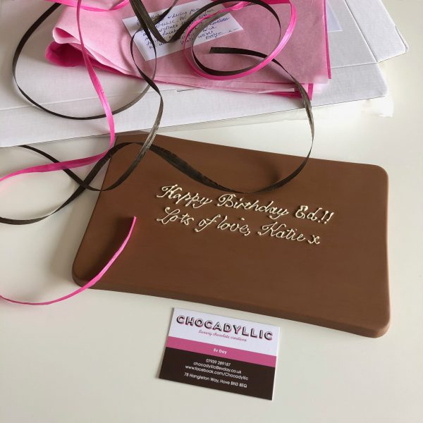 chunky milk chocolate big 500g milk tablet measures 254x152x10mm with pretty personalised happy birthday message pink and brown raffia ribbons, pink tissue paper, and white postal box all biodegradable and eco friendly